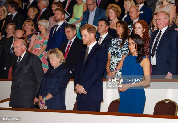 Prince Harry Duke of Sussex and Meghan Duchess of Sussex stand for the National Anthem ahead of the '100 days of peace' concert to commemorate the...