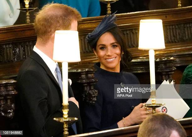 Prince Harry Duke of Sussex and Meghan Duchess of Sussex take their seats ahead of the wedding of Princess Eugenie of York and Mr Jack Brooksbank at...