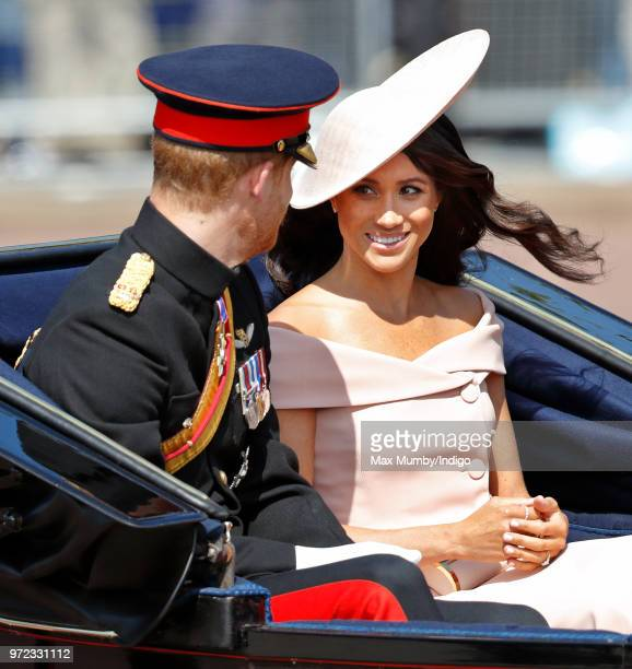 Prince Harry Duke of Sussex and Meghan Duchess of Sussex travel down The Mall in a horse drawn carriage during Trooping The Colour 2018 on June 9...