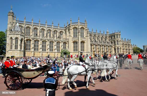 Prince Harry Duke of Sussex and Meghan Duchess of Sussex travel in an Ascot Landau carriage past St George's Chapel as they begin their procession...