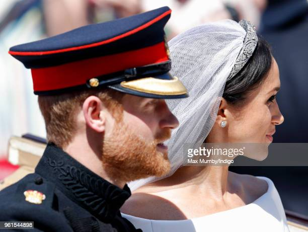 Prince Harry Duke of Sussex and Meghan Duchess of Sussex travel in an Ascot Landau carriage as they begin their procession through Windsor following...