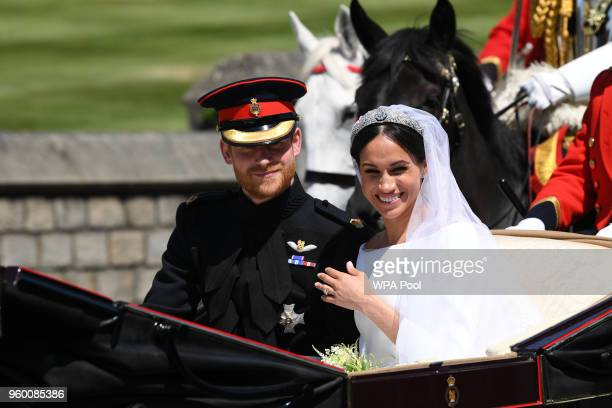 Prince Harry Duke of Sussex and Meghan Duchess of Sussex travel in the Ascot Landau Carriage during their carriage procession on Castle Hill outside...