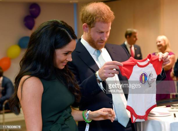 Prince Harry, Duke of Sussex and Meghan, Duchess of Sussex view a gift for their son Archie as they attend the WellChild awards at Royal Lancaster...