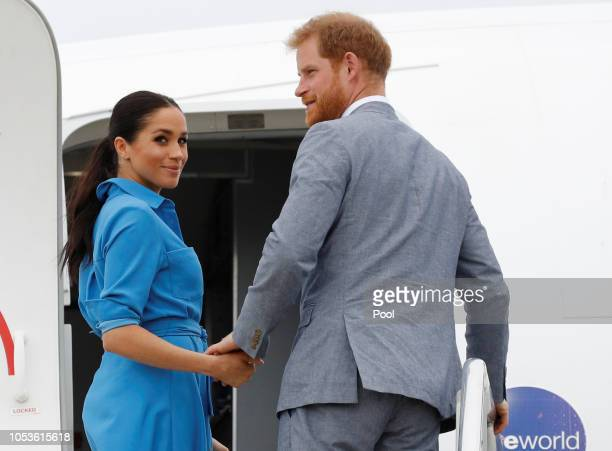 Prince Harry Duke of Sussex and Meghan Duchess of Sussex walk together ahead of Tonga's Princess Angelika as they depart from Fua'amotu International...
