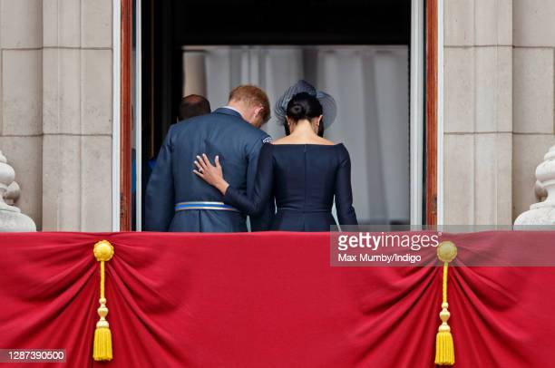 Prince Harry, Duke of Sussex and Meghan, Duchess of Sussex walk back inside Buckingham Palace after watching a flypast to mark the centenary of the...