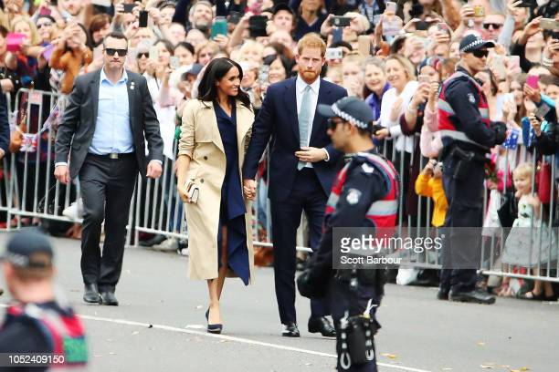 Prince Harry Duke of Sussex and Meghan Duchess of Sussex walk past fans outside Government House on October 18 2018 in Melbourne Australia The Duke...