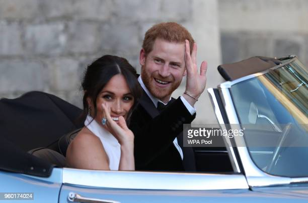 Prince Harry Duke of Sussex and Meghan Duchess of Sussex wave as they leave Windsor Castle after their wedding to attend an evening reception at...