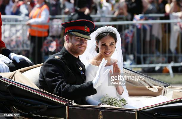 Prince Harry, Duke of Sussex and Meghan, Duchess of Sussex wave from the Ascot Landau Carriage during their carriage procession on Castle Hill...