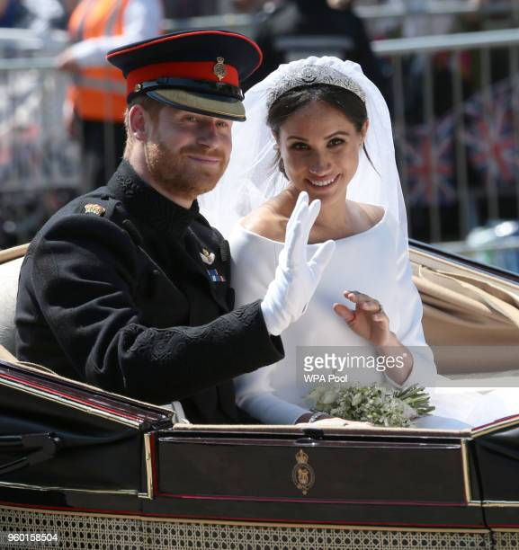 Prince Harry Duke of Sussex and Meghan Duchess of Sussex wave from the Ascot Landau Carriage during their carriage procession on Castle Hill outside...