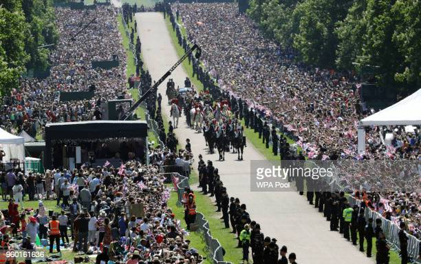 Prince Harry Duke of Sussex and Meghan Duchess of Sussex wave from the Ascot Landau Carriage during their carriage procession after their wedding at...
