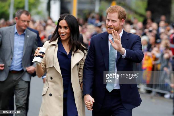 Prince Harry, Duke of Sussex and Meghan, Duchess of Sussex wave to the crowd as they arrive at the Royal Botanic Gardens on October 18, 2018 in...