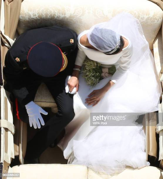 Prince Harry, Duke of Sussex and the Duchess of Sussex hold hands in the Ascot Landau Carriage as their carriage procession rides along the Long...