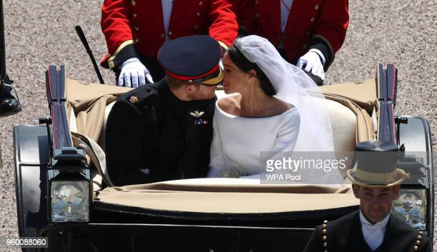 Prince Harry Duke of Sussex and the Duchess of Sussex kiss in the Ascot Landau Carriage as their carriage procession rides along the Long Walk on May...