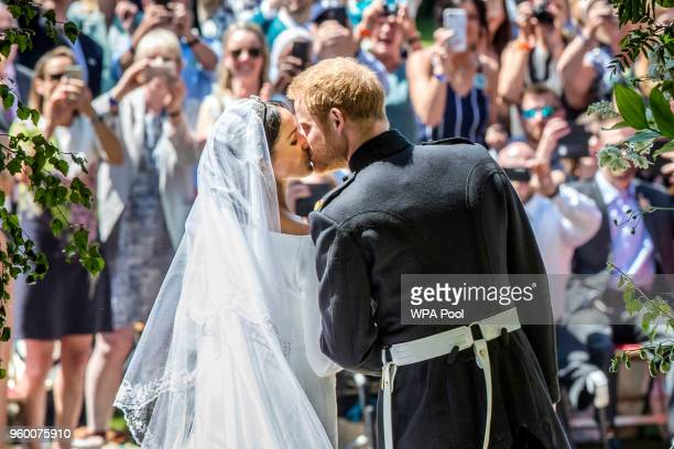 Prince Harry Duke of Sussex and The Duchess of Sussex kiss on the steps of St George's Chapel in Windsor Castle after their wedding on May 19 2018 in...