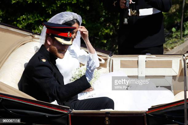 Prince Harry Duke of Sussex and The Duchess of Sussex leave Windsor Castle in the Ascot Landau carriage during a procession after getting married at...