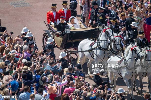 Prince Harry, Duke of Sussex and The Duchess of Sussex meet the crowds as they leave Windsor Castle in the Ascot Landau carriage during a procession...