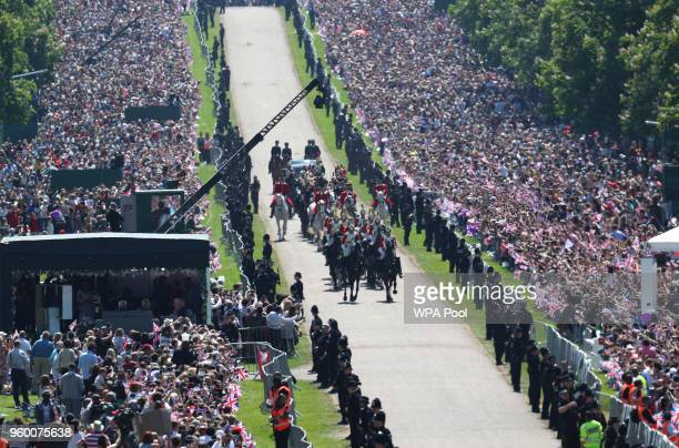 Prince Harry Duke of Sussex and The Duchess of Sussex ride along the Long Walk in the Ascot Landau carriage during a procession after getting married...