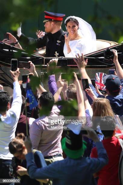 Prince Harry, Duke of Sussex and The Duchess of Sussex ride in the Ascot Landau carriage during the procession after getting married St George's...