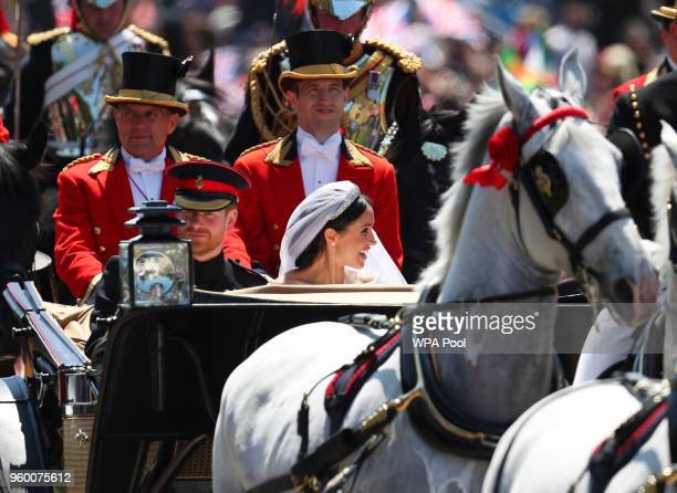 Prince Harry Duke of Sussex and The Duchess of Sussex ride in the Ascot Landau carriage during a procession after getting married at St Georges...