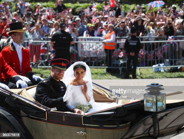 Prince Harry, Duke of Sussex and The Duchess of Sussex ride in the Ascot Landau carriage during a procession after getting married at St Georges...