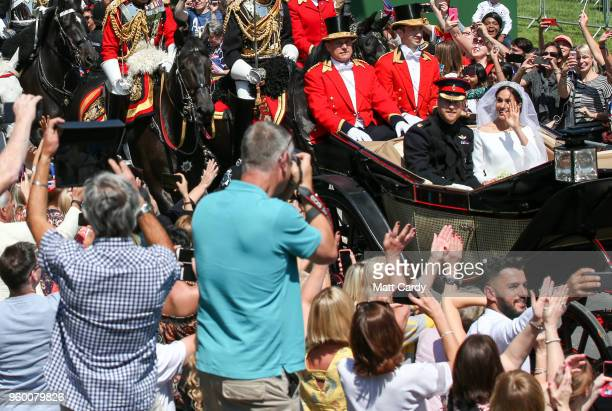 Prince Harry Duke of Sussex and The Duchess of Sussex ride in the Ascot Landau carriage during the procession after getting married St George's...