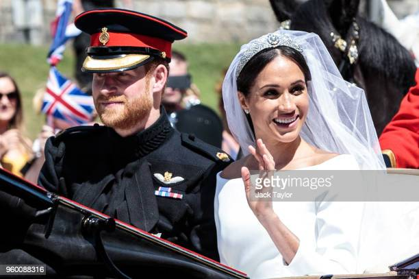 Prince Harry Duke of Sussex and the Duchess of Sussex ride in the Ascot Landau carriage during the procession after getting married at St George's...