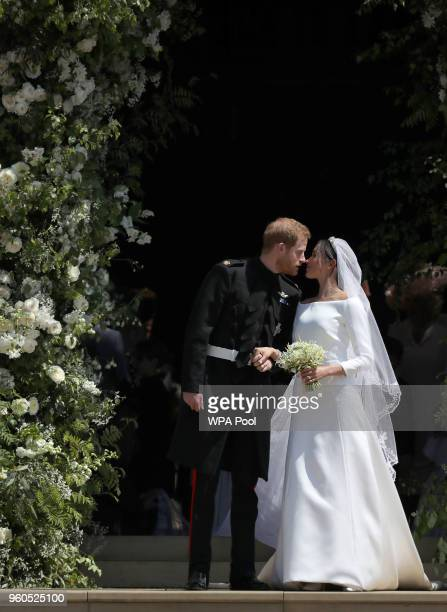Prince Harry, Duke of Sussex and The Duchess of Sussex share a kiss after their wedding at St George's Chapel at Windsor Castle on May 19, 2018 in...