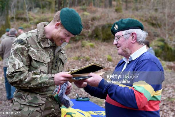 Prince Harry Duke of Sussex Captain General Royal Marines receives a gift of a rugby shirt and a picture from former Marine Yorkie Malone during his...
