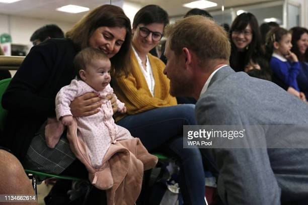 Prince Harry Duke of Sussex chats with 3 months old baby Naz and mother Maria Ahmad as they watch a ballet class for 4 to 6 year olds during a visit...