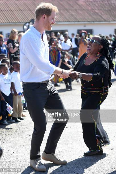 Prince Harry, Duke of Sussex dances with locals as he visits a Justice Desk initiative in Nyanga township with Meghan, Duchess of Sussex, during...