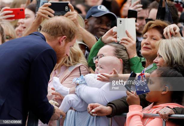 Prince Harry Duke of Sussex greets a baby as he arrives at the Royal Botanic Gardens on October 18 2018 in Melbourne Australia The Duke and Duchess...