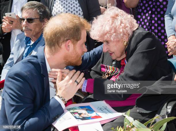 Prince Harry Duke of Sussex greets royal fan and war widow Daphne Dunne as they arrive for a public walkabout at the Sydney Opera House on October 16...