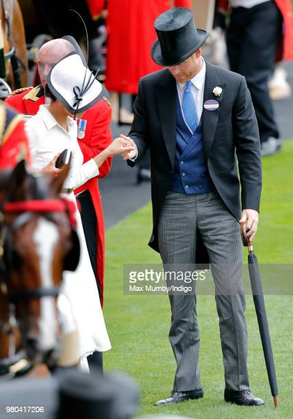 Prince Harry Duke of Sussex helps Meghan Duchess of Sussex to climb out of a horse drawn carriage on day 1 of Royal Ascot at Ascot Racecourse on June...