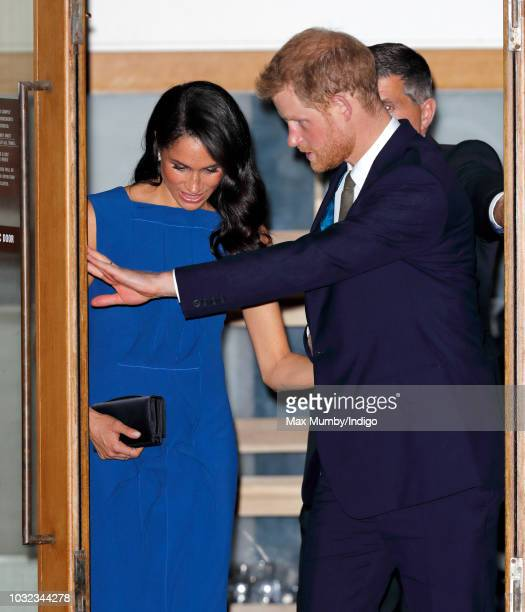 Prince Harry Duke of Sussex holds open the door for Meghan Duchess of Sussex as they depart the '100 Days of Peace' concert to commemorate the...