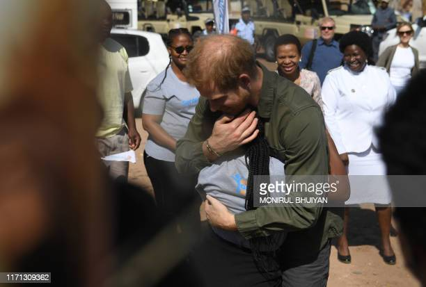 Prince Harry Duke of Sussex hugs a child on his arrival at The Princes' foundation for children in Africa Sentebale at the Chobe district in the...
