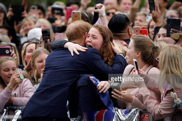 Prince Harry Duke of Sussex hugs a member of the public as he arrives at the Royal Botanic Gardens on October 18 2018 in Melbourne Australia The Duke...