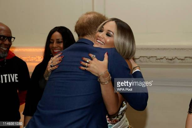 Prince Harry Duke of Sussex hugs British singer Rita Ora during a reception before The Sentebale Audi Concert at Hampton Court Palace on June 11 2019...