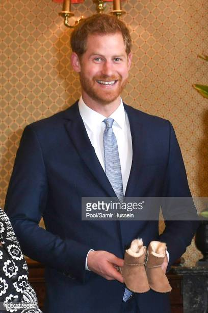 Prince Harry Duke of Sussex is given a gift from Australia's Governor General Peter Cosgrove and wife Lynne Cosgrove at Admiralty House on October 16...