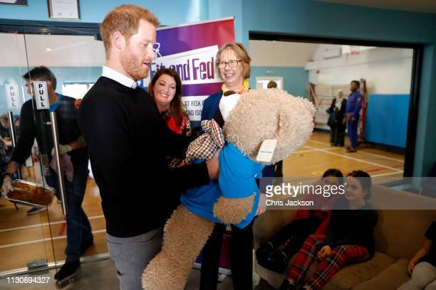 Prince Harry Duke of Sussex is given the gift of a large teddy during his visit to a 'Fit and Fed' halfterm initiative in Streatham on February 19...