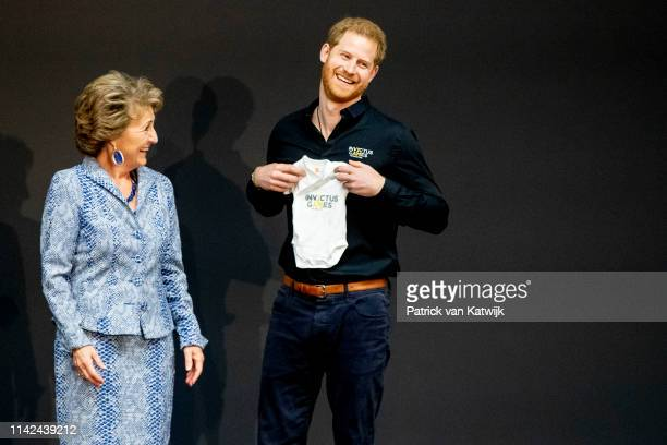 Prince Harry Duke of Sussex is presented with an Invictus Games baby grow for his newborn son Archie by Princess Margriet of The Netherlands during...