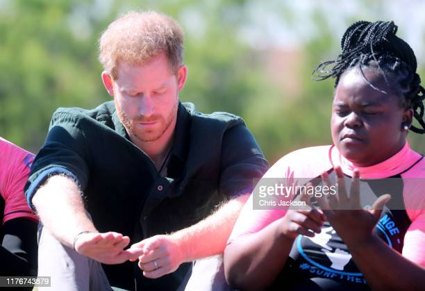 Prince Harry, Duke of Sussex joins surf mentors and participates in a group activity to promote positive thinking, with Meghan, Duchess of Sussex, as...