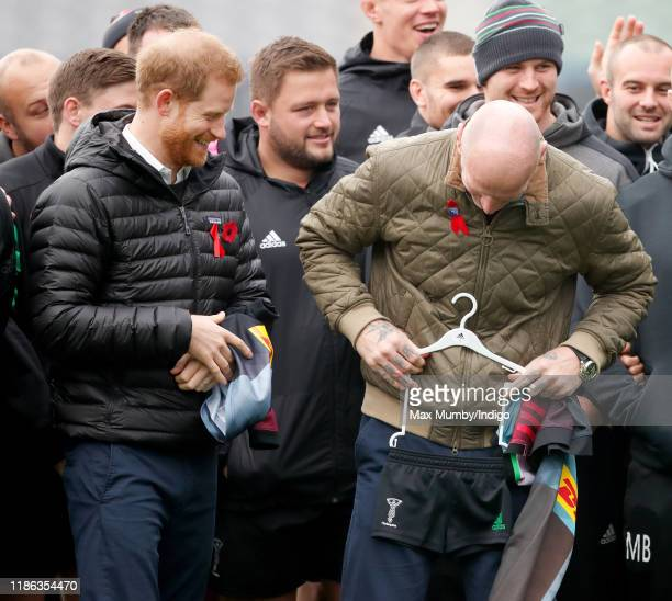 Prince Harry, Duke of Sussex jokes with Gareth Thomas after being presented with a Harlequins rugby kit for baby son Archie Harrison...