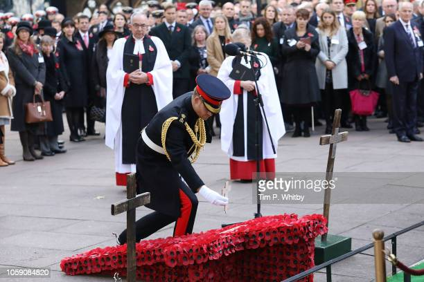 Prince Harry Duke of Sussex lays a wooden cross as he attends the field of remembrance service at Westminster Abbey on November 8 2018 in London...