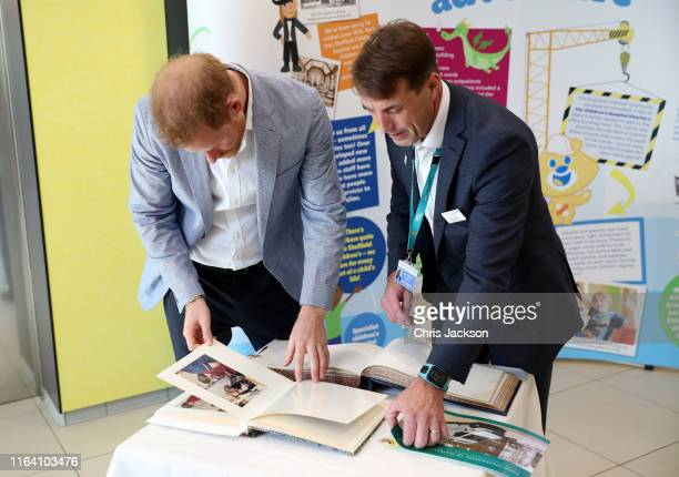 Prince Harry, Duke of Sussex looks at photos of when his mother, Princess Diana, visited the hospital 30 years ago, during a visit to Sheffield...
