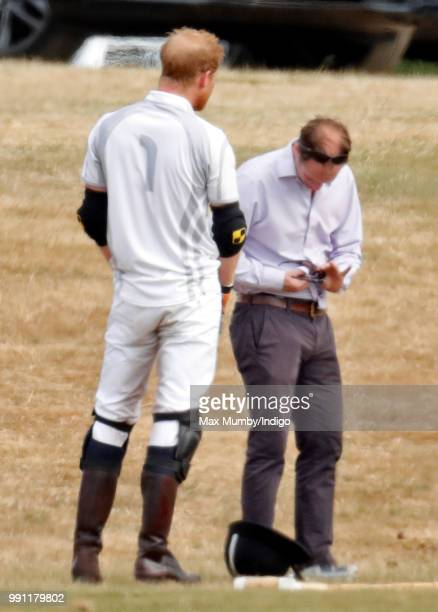 Prince Harry Duke of Sussex looks on as he has his sunglasses cleaned for him by his polo manager Andrew Tucker during the Audi Polo Challenge at...