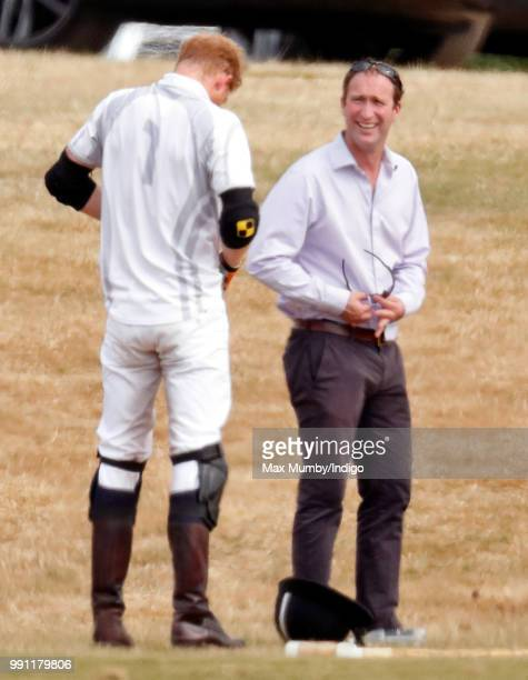 Prince Harry, Duke of Sussex looks on as he has his sunglasses cleaned for him by his polo manager Andrew Tucker during the Audi Polo Challenge at...