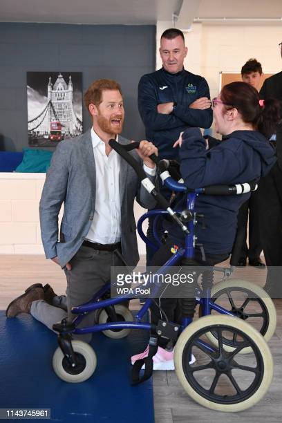 Prince Harry Duke of Sussex meets a participant of the Rebound Therapy session as he visits the OXSRAD Disability Sports and Leisure Centre on May 14...