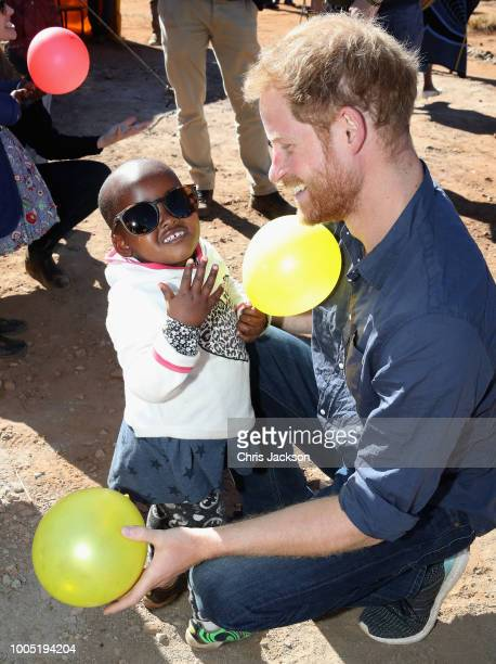 Prince Harry Duke of Sussex plays with children holding balloons during the official opening of The Dining Hall at Phelisanong Children's Home on...