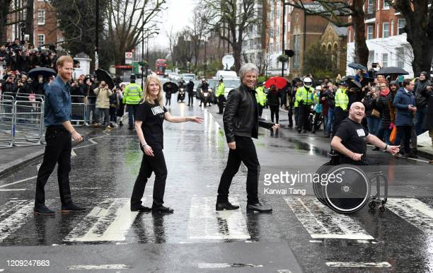 Prince Harry Duke of Sussex poses with Jon Bon Jovi and members of the Invictus Games Choir on the zebra crossing outside Abbey Road Studios on...