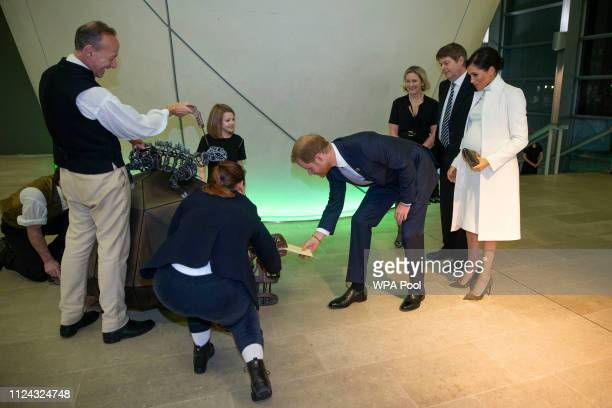 Prince Harry Duke of Sussex reaches for his ticket from a Turtle puppet as Meghan Duchess of Sussex looks on as they attend a gala performance of...